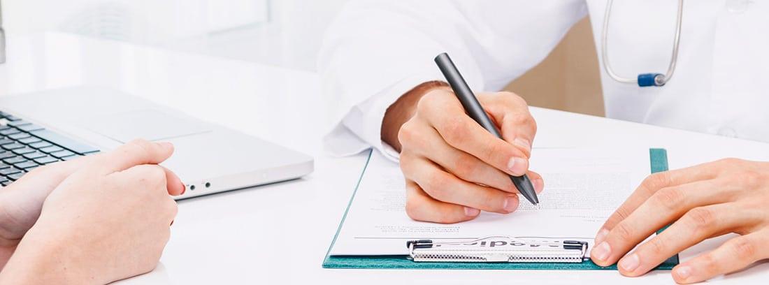 Médico firmando un documento