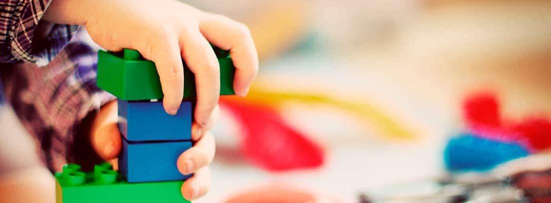Manos de niño jugando con unas construcciones