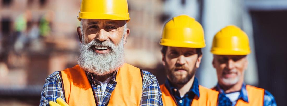 Obreros ataviados con casco y guantes