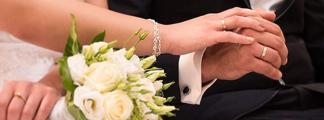Detalle de novios en su boda con un ramo