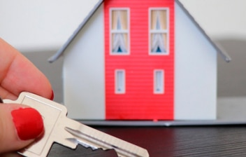 Mano con unas llaves y maqueta de una casa al fondo