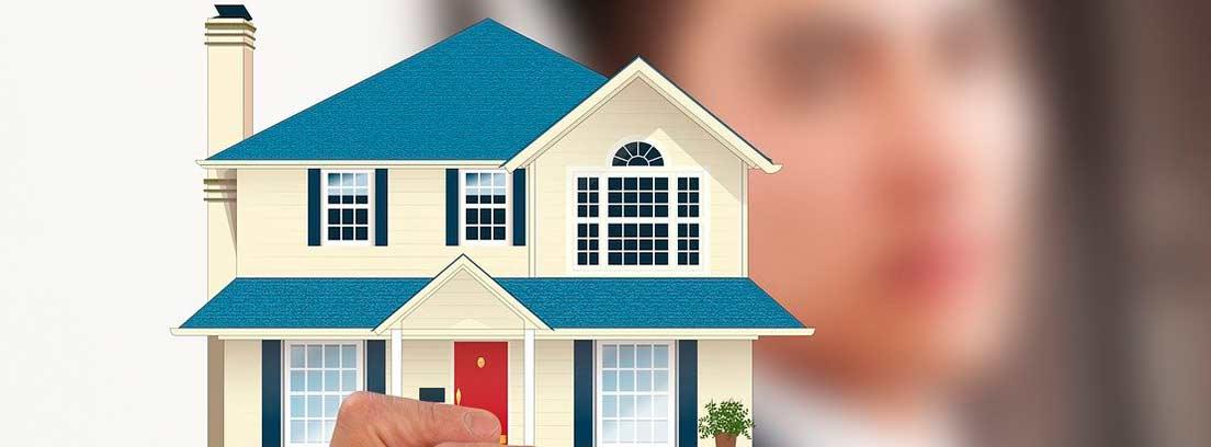 Mano sujetando un dibujo de una casa
