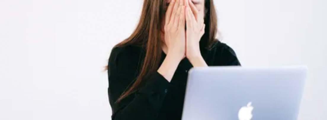 Una mujer expresa cansancio frente al ordenador