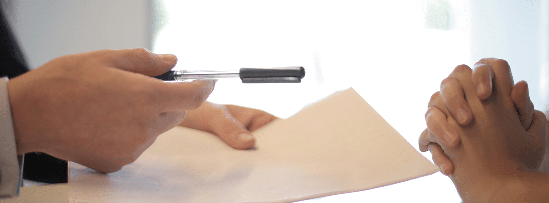 Un profesional ofrece al cliente un bolígrafo para la firma de un documento