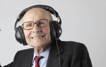 Anciano con traje y corbata escucha música y baila