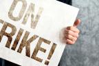"""Manos sujetando un cartel en el que se lee: """"on strike!"""""""