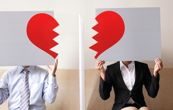 Pareja sentada en un sofá sujetando un cartel con un corazón roto