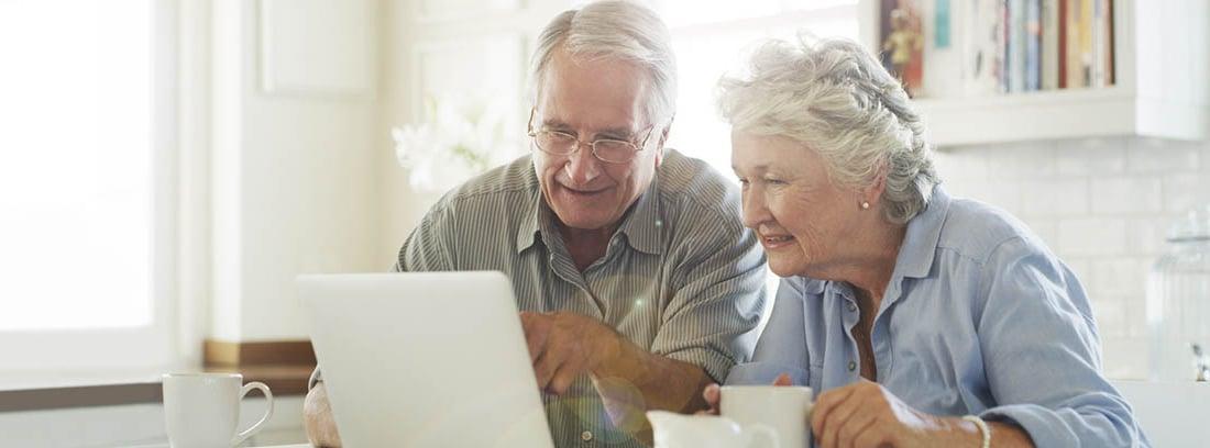 Pareja de edad madura consultando en ordenador