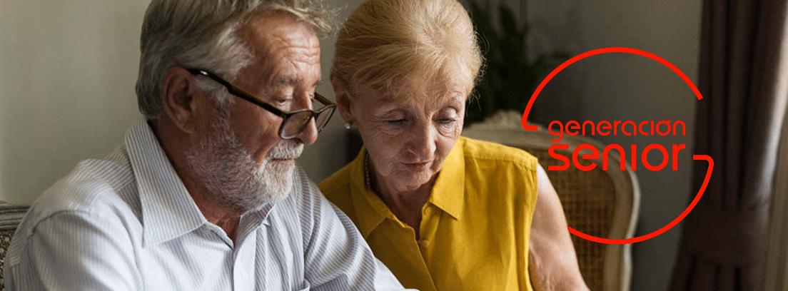 Cuanto se r3educe la jubilación anticipada: pareja de senior sentados mirando papeles