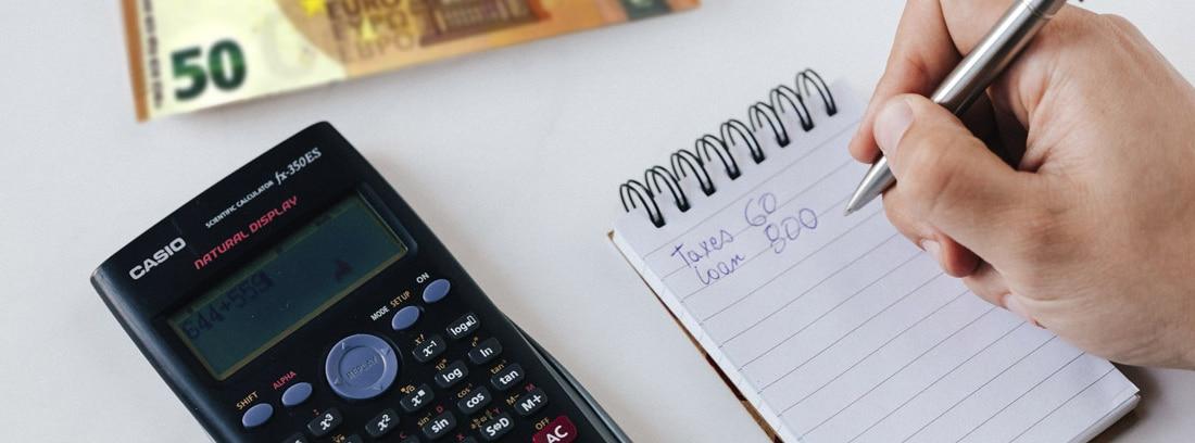 Billetes de dólar, calculadora y libreta