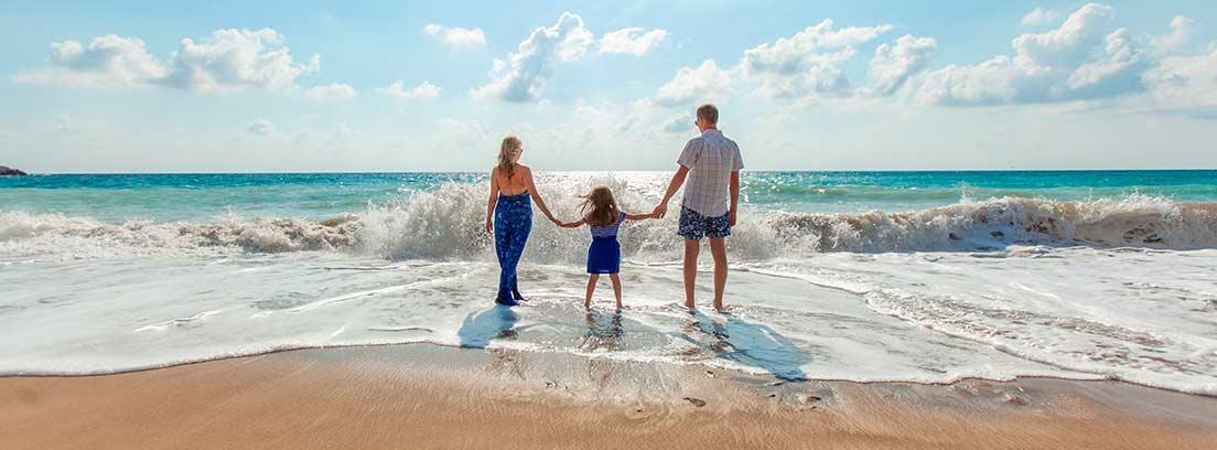 Mujer, hombre y niña cogidos de la mano en la playa mirando el mar