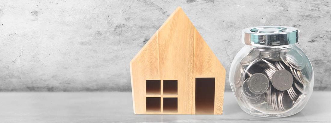 Casa de madera en miniatura y recipiente con monedas
