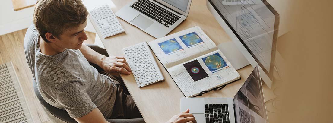 Un trabajador con dos ordenadores y una pantalla