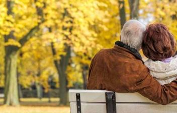Hombre y mujer mayores sentados en un banco en un parque otoñal