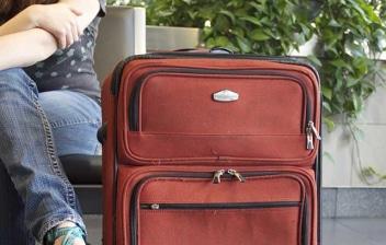 Vista parcial de una mujer sentada y una maleta
