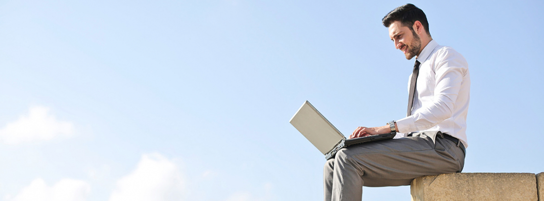 Hombre sentado sobre unos ladrillos con un ordenador en las rodillas