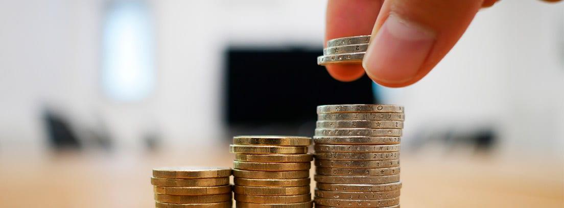 Mano colocando columnas de monedas en sentido creciente