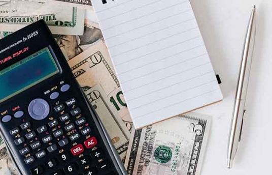 Calculadora y billetes de dólar