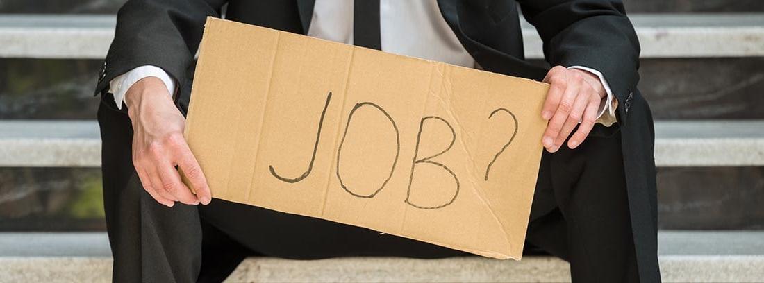 """Hombre con traje sujetando un cartel en el que puede leerse: """"Job?"""""""
