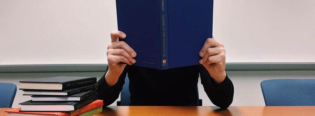 Hombre tapándose la cara con un libro