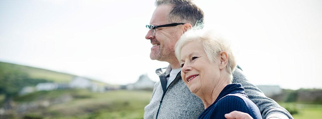 Hombre y mujer mayores abrazados en el campo