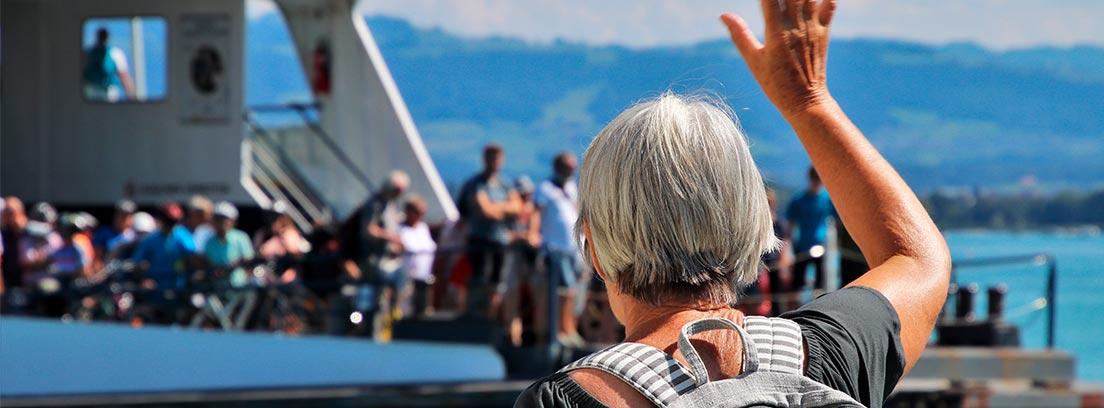 Mujer mayor saludando a un barco lleno de gente