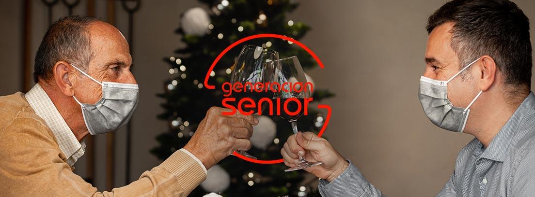 Hombre mayor y joven con mascarilla brindando con una copa de vino delante de un pino de Navidad