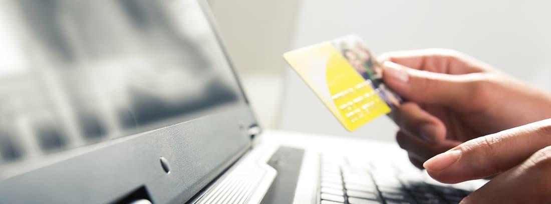 Manos sosteniendo una tarjeta y tecleando en un portátil