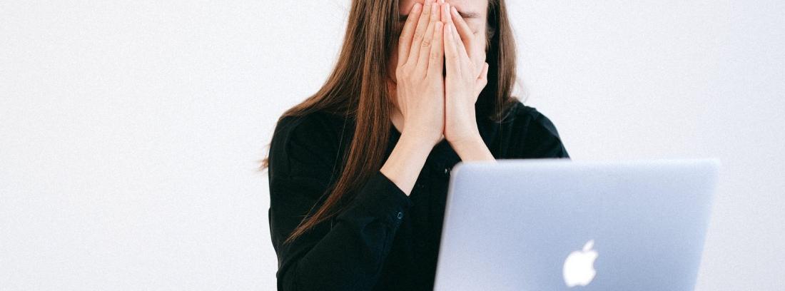 Mujer se cubre la cara frente al ordenador