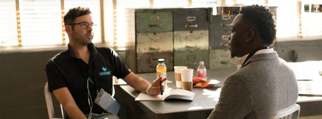 Dos adultos conversan mientras toman un café