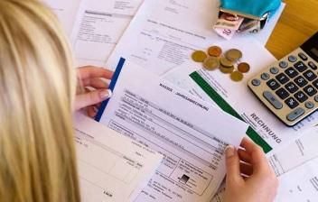 Mujer revisando facturas con una calculadora y un monedero