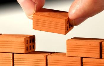 Dedos colocando un ladrillo en una pared de miniatura