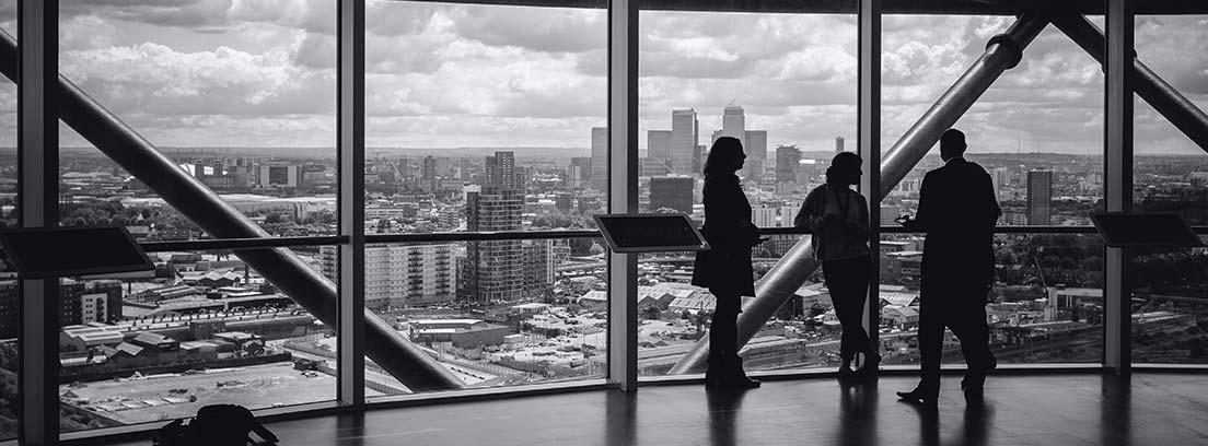 Tres personas en una planta alta de edificio de oficinas