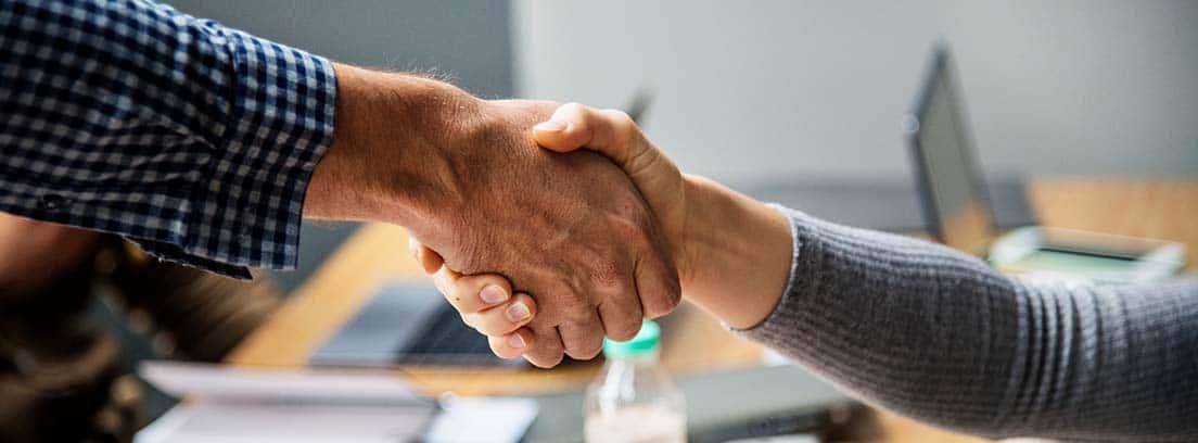 Dos personas estrechando las manos en un entorno de trabajo
