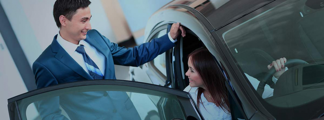 Hombre de pie junto a una mujer probando un coche nuevo