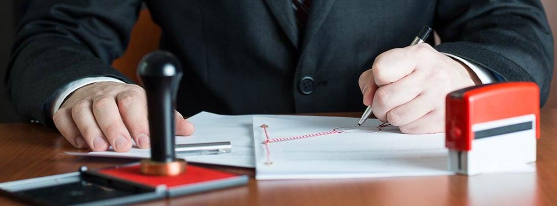 Notario firmando unos documentos