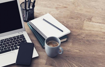Ordenador, móvil, taza de café y cuaderno