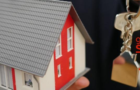 Hombre sujetando la maqueta de una casa y unas llaves