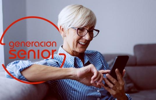 Mujer con pelo blanco mirando sonriente un teléfono móvil