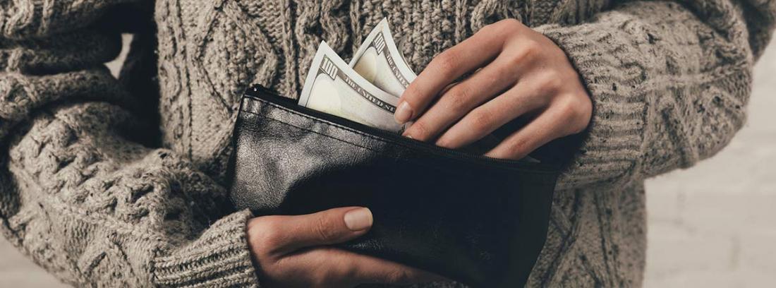 Mujer guardando unos billetes en una cartera