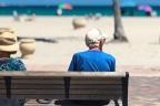 Dos ancianos en un banco con vistas a la playa