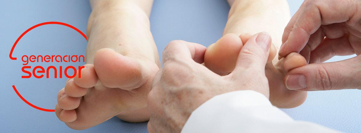 Manos de un podólogo haciendo un tratamiento en unos pies