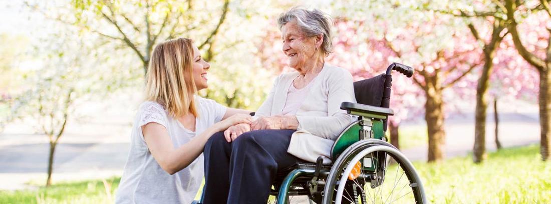 Mujer joven sonriendo a una mujer mayor sentada en una silla de ruedas