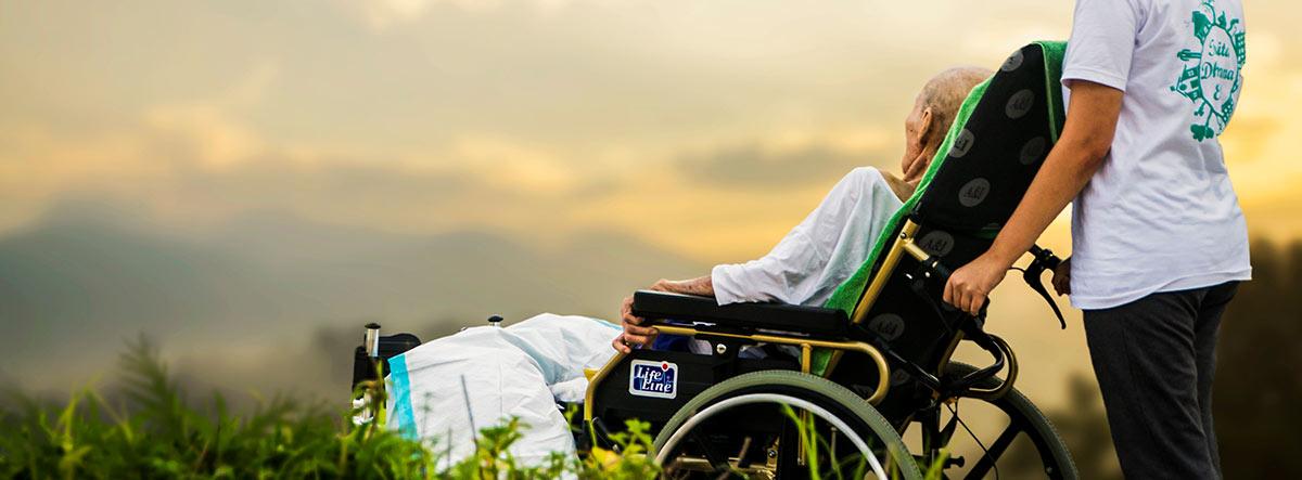 Mujer llevando a otra mujer con una silla de ruedas en el campo