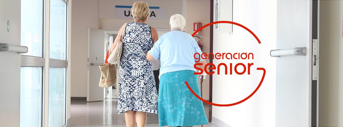 Mujer de la mano con otra mujer mayor caminando por el pasillo de un centro médico