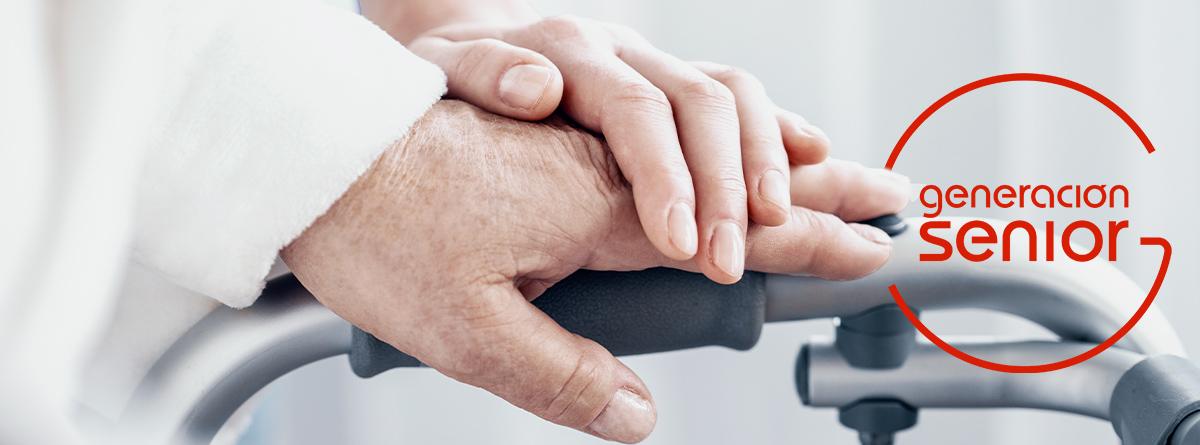 Mano de una persona mayor sobre un andador y mano de una cuidadora