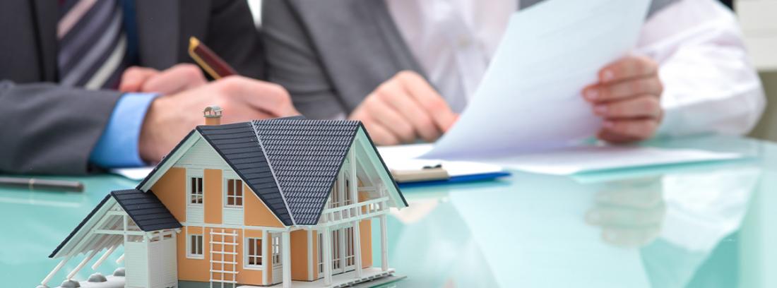 dos personas firmando un documento con una casa en miniatura