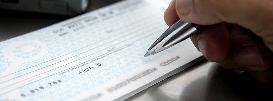 persona firmando un cheque