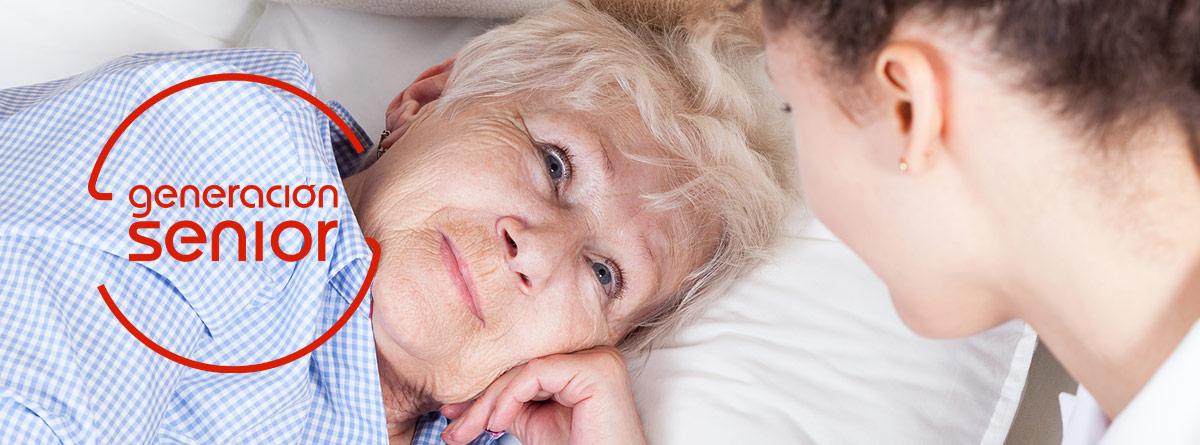 Mujer joven mirando a mujer mayor en la cama