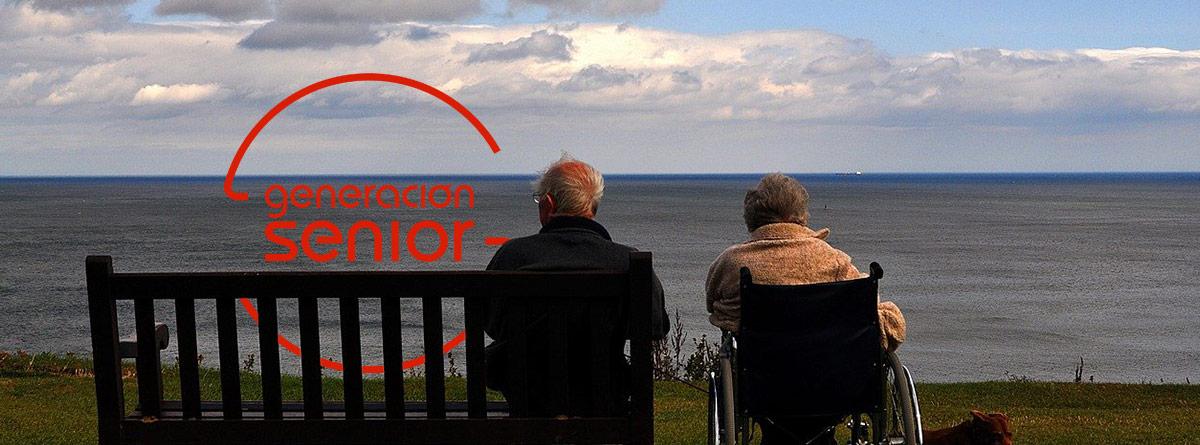 Hombre mayor junto a mujer en silla de ruedas mirando el mar
